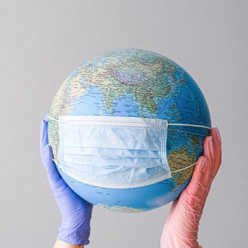 hands-with-latex-gloves-holding-a-globe-with-a-face-mask-4167544-scaled